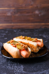 Photo of hotdogs on black plate