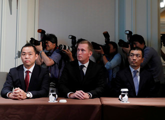 Photographers take a picture behind Mercari Inc.'s executives at a news conference after a ceremony to mark the company's debut on the Tokyo Stock Exchange in Tokyo