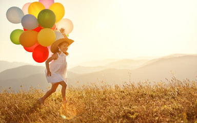 happy child with balloons at sunset in summer.
