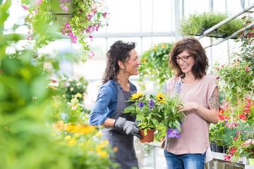 Floristin mit Kundin beim Verkaufsgespräch haben Spaß und lachen