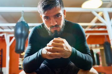 Confident bearded man in sportswear sitting with hands together and looking at camera on background of boxing gym interior.
