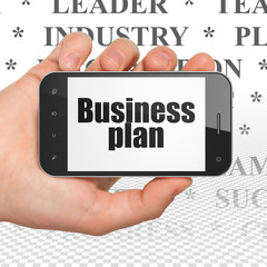 Business concept: Hand Holding Smartphone with  black text Business Plan on display,  Tag Cloud background, 3D rendering