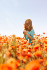 Young woman sniffing a poppy in meadow.