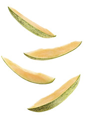 sliced flying melon isolated on white background. cut melon fruit in pieces isolated on white background. Levity fruit floating in the air