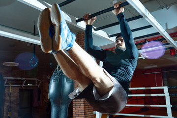 From below of sportive man hanging on bars and lifting legs up working out on abdomen.