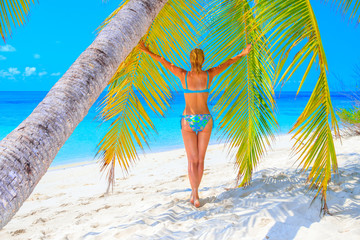 Beautiful laughing blond woman with bikini on a palm tree on the sandy beach