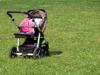 Empty baby carriage on the green grass. Stroller on summer lawn, environment friendly concept. Kidnapping a child, lost children