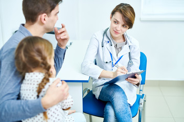 Crop view of female doctor sitting in office and listening to little patient