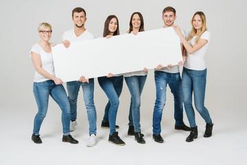 gruppe trägt gemeinsam ein weißes, leeres plakat