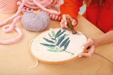 Floral picture. Skillful red-haired housewife wearing knitted red sweater embroidering little beautiful floral picture