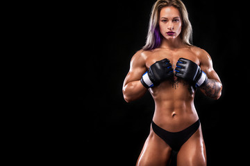 Muscular young fitness sports woman with strong fit body on black background.