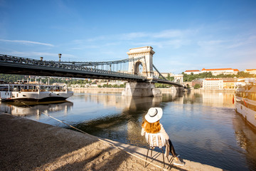 Young woman tourist enjoying morning view on the old town with Chain bridge and river traveling in Budapest city, Hungary