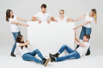 lachende freunde in jeans halten ein großes leeres schild