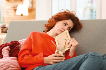 Chocolate cream. Red-haired appealing student eating tasty sweet chocolate cream lying on comfortable sofa while watching photos