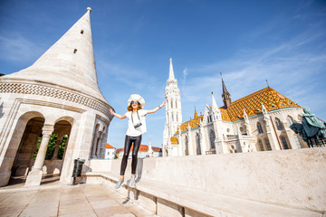 Happy young woman tourist on the Fisherman's bastion in fron of the church traveling in Budapest, ungary