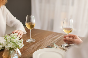 Young couple with glasses of delicious wine in restaurant