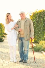 Senior man with cane and nurse from care home walking in park