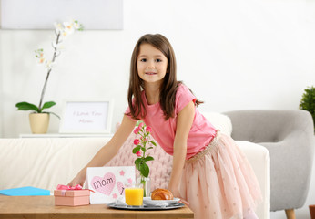 Little girl preparing surprise for her mommy on Mother's Day indoors