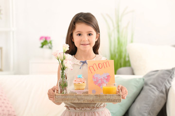 Little girl holding tray with breakfast and greeting card for her mommy on Mother's Day indoors