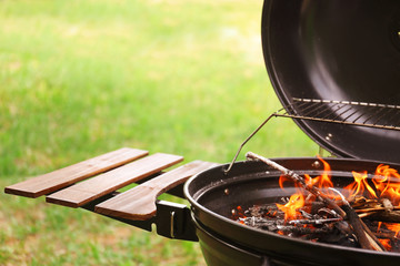 Modern barbecue grill with fire flames outdoors
