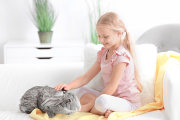 Little girl with adorable rabbit on sofa in room