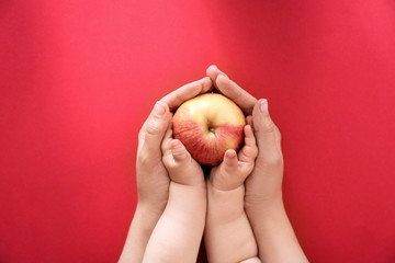 Young woman and little child holding apple on color background, top view. Healthy diet