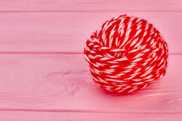 Red ball of yarn and copy space. Ball of soft woolen threads for knitting on pink wooden background, text space.