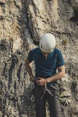 A Man Climber Fixing His Equipment