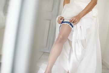 dettaglio di sposa che indossa la giarrettiera sotto l'abito