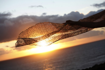 dettaglio del velo di un  abito da sposa che sventola con dietro il tramonto