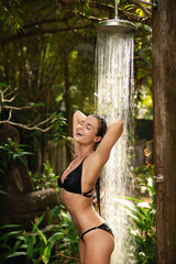Woman taking shower in tropical garden in resort