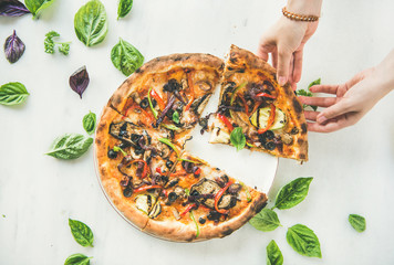 Summer dinner or lunch. Flat-lay of female hands taking freshly baked Italian vegetarian pizza with vegetables and fresh basil over white marble table, top view