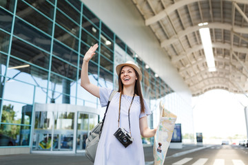 Traveler tourist woman with retro vintage photo camera, paper map waving hand for greeting, meeting friend and catch taxi at airport. Passenger traveling abroad on weekend getaway. Air flight concept.