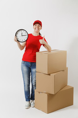 Full length portrait of delivery woman in red cap, t-shirt isolated on white background. Female courier near empty cardboard boxes, holding round clock, showing in time. Receiving package. Copy space.