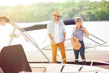 Young couple preparing on the dock is preparing to sail