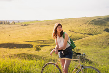 Girl with bicycle in beautiful rural landscape at sunset. Young pretty female person with retro bike standing in a meadow on bright sunny afternoon in summer