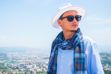 A young guy in a scarf and hat on Mount Tibidabo in Barcelona, Spain