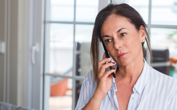 Middle aged woman using smartphone with a confident expression on smart face thinking serious