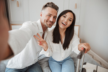 Excited young couple taking selfie with mobile phone
