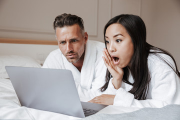 Surprised young couple dressed in bathrobes lying on bed
