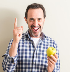 Senior man holding a green apple surprised with an idea or question pointing finger with happy face, number one