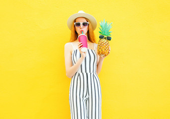 Fashion pretty woman with a pineapple, cup of juice in white striped pants, round hat on yellow background