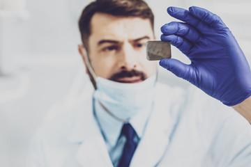 Analyzing roentgen. Attentive brunette dentist raising his hand while examining bad teeth