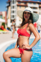 A Sexy lady in a big beach hat get out of the swimming pool