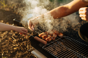 Close up of a woman's hand grilling bacon strips and sausages on barbeque grill