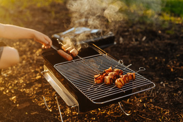 Close up of woman's hand grilling sausages and bacon strip on barbeque grill
