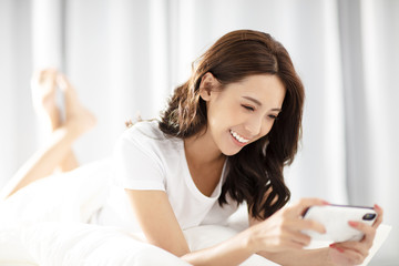 young woman lying on the bed and playing the phone