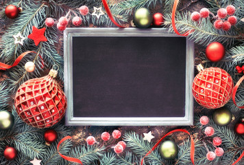 Fir twig decorated with baubles, berries and stars, black-board, text space