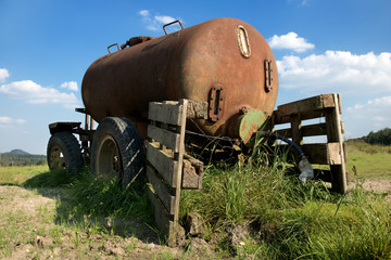 Old mobile cistern with water on the countryside. Abandoned old rusty car trailer tank in the field.