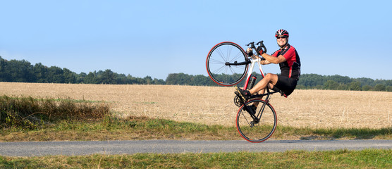Photo sur Aluminium Cyclisme Cheerful cyclist riding on the rear wheel. Biker balancing while driving on a road bike. Risky ride on one wheel.